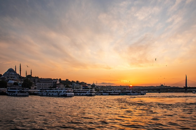 Paisaje soleado de verano en estambul en la puesta de sol. atraviese el bósforo con vistas a la mezquita azul. un barco con turistas navega bajo el puente