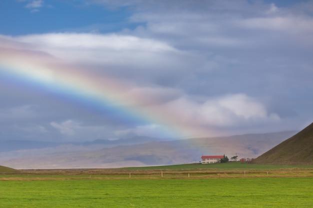 Paisaje del sur de islandia con una casa y un arco iris