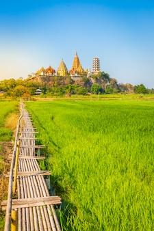 Paisaje del templo de wat tham sua (templo de la cueva del tigre) con campos de arroz jazmín
