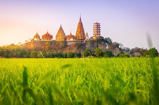 Paisaje del templo de wat tham sua (templo de la cueva del tigre) en escena del atardecer con campos de arroz jasmine