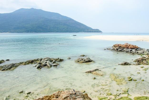 Paisaje tropical de mar con montañas y rocas.