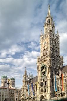 Paisaje urbano con alta toalla del edificio central del nuevo ayuntamiento en la plaza marienplatz sobre un fondo de cielo nublado azul, munich, baviera, alemania