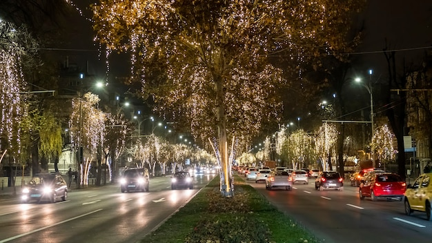 Paisaje urbano de la ciudad por la noche, coches en movimiento en la carretera, mucha iluminación navideña en bucarest, rumania