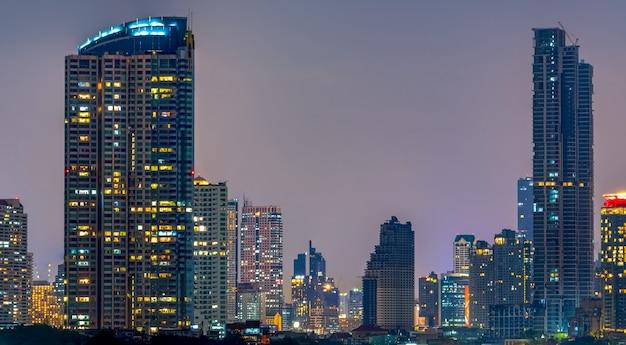 Paisaje urbano del edificio moderno cerca del río en la noche. edificio de oficinas de arquitectura moderna. rascacielos con cielo nocturno. fotografía nocturna del edificio frente al río. condominio abierto de luz en la noche.