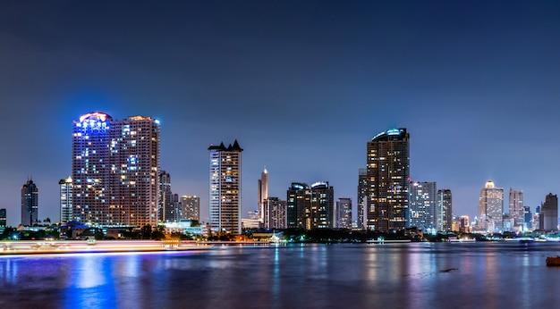 Paisaje urbano del edificio moderno cerca del río en la noche. edificio de oficinas de arquitectura moderna. rascacielos con cielo nocturno.