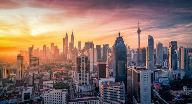 Paisaje urbano del horizonte de la ciudad de kuala lumpur con la piscina en el top del tejado del hotel en la salida del sol en malasia.