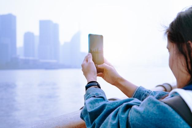 Paisaje urbano en el teléfono inteligente. ver a través de la pantalla en la ciudad de shanghai en la pantalla de mujeres, china.