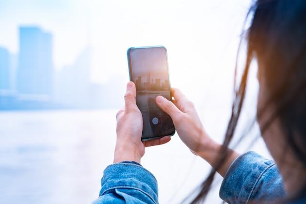 Paisaje urbano en el teléfono inteligente. ver a través de la pantalla en la ciudad de shanghai en la pantalla de mujeres