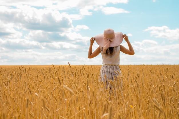 Paisaje de verano de un campo de trigo de color dorado y azul cielo. una mujer se para con un sombrero de paja y un vestido de verano se ve en el horizonte.