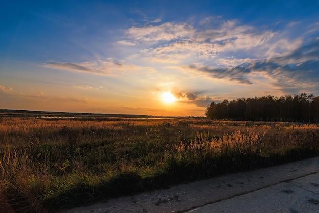 Paisaje de verano con prado y hermosa puesta de sol con bosque y río