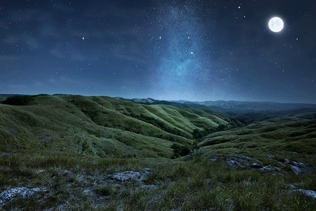 Paisaje de verdes colinas con estrellas.