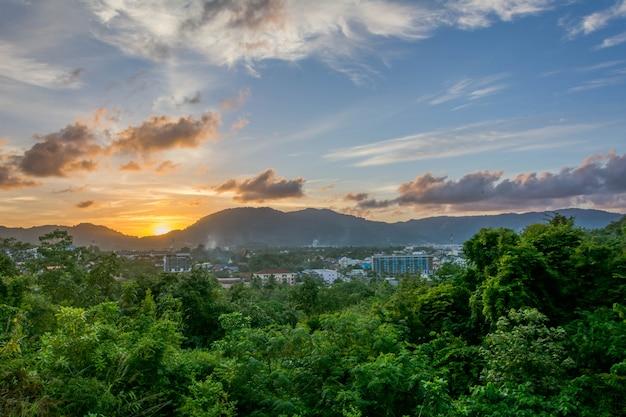 Paisajes ciudad puesta de sol sobre montaña