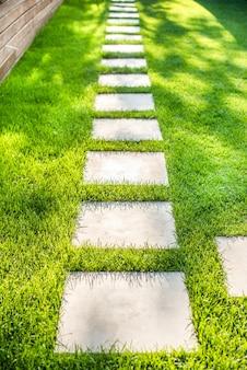 Paisajismo del jardín con un recorrido de paletas individuales. cuadrados de piedra en el césped. verano, pasto verde, resplandor del sol.
