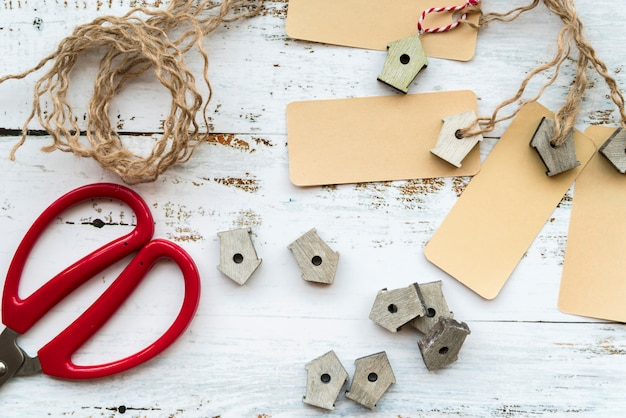 Pajareras en miniatura; etiquetas cuerda y tijeras en escritorio blanco