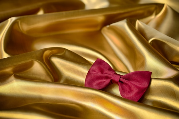 Pajarita roja sobre fondo de tela dorada