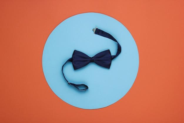 Pajarita sobre papel coral con círculo azul en el medio.