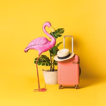 Pájaro decorativo, planta de maceta y maleta.