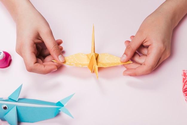 Pájaro femenino hecho a mano de papel de origami sobre fondo rosa