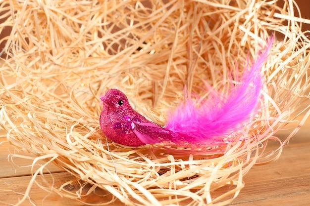 Pájaro en nido de paja con plumas rosas y purpurina