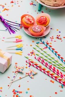 Pajitas de beber; apuntalar; velas; magdalena caja de regalo; y confeti sobre fondo azul