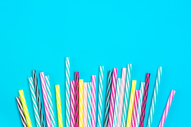 Pajitas con rayas para fiesta sobre fondo azul.
