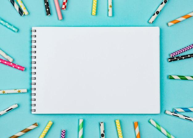 Pajitas con vista superior de bloc de notas vacío