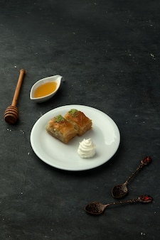 Pakhlava turco con miel sobre la mesa