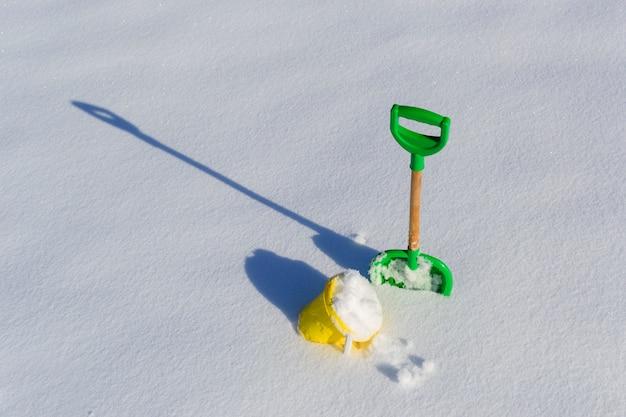 Pala y cubo de plantilla en nieve profunda fresca copia espacio