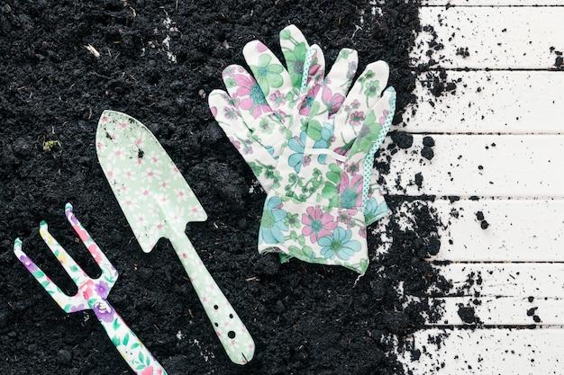 Pala de jardineria; horquilla de tono y guantes de mano sobre tierra encima del banco de madera.