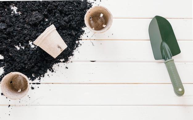 Pala de jardineria; macetas de turba de plántulas; y suelo sobre banco de madera