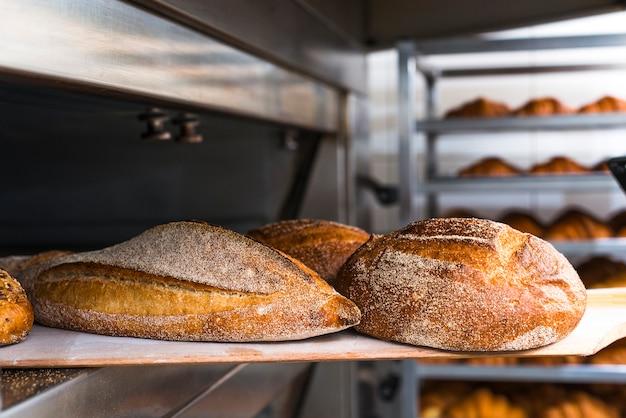Pala de madera con pan recién horneado del horno.