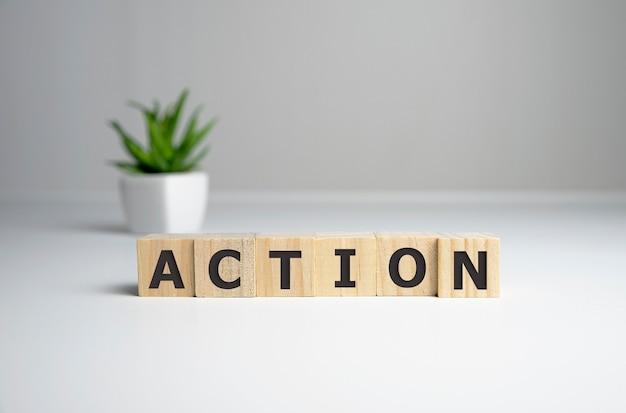 Palabra de acción escrita sobre un bloque de madera