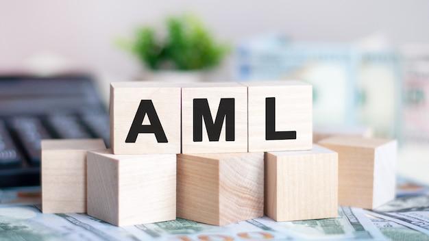 La palabra aml en cubos de madera, billetes y calculadora en el fondo. aml - abreviatura de anti-lavado de dinero.