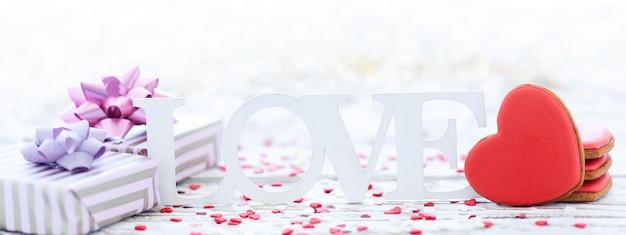 La palabra amor con corazón de galletas y caja de regalo en mesa de madera. concepto de día de san valentín. bandera.