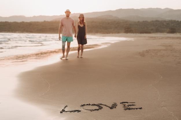 Palabra amor en la costa de arena y pareja amorosa borrosa en fondo caminando