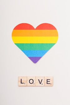 Palabra amor en cubos de madera y corazón lgbt.
