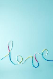 Palabra de amor escrita con letras de hilo de lana, concepto y fondo para el día de san valentín