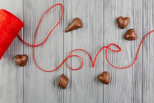 Palabra amor hecha de hilo rojo entre chocolates.