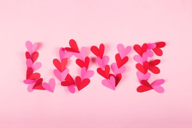 Palabra amor hecho de corazones de papel sobre un fondo rosa.