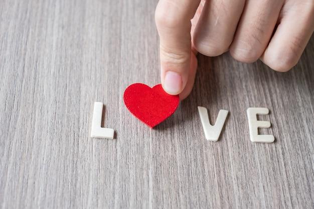 Palabra de amor de las letras del alfabeto de madera con mano de mujer con corazón rojo
