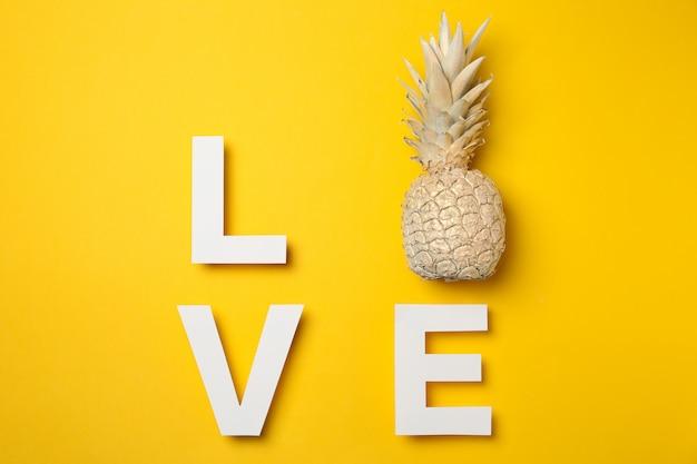 Palabra amor con piña pintada sobre fondo amarillo, espacio para texto
