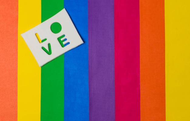 Palabra de amor en tableta y brillante bandera lgbt
