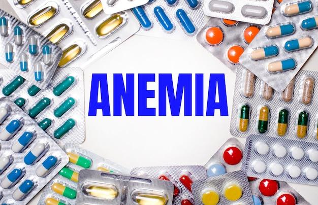 La palabra anemia está escrita sobre un fondo claro rodeado de paquetes multicolores con píldoras. concepto medico