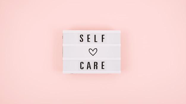Palabra de autocuidado en caja de luz y narcisos de flores sobre fondo rosa endecha plana
