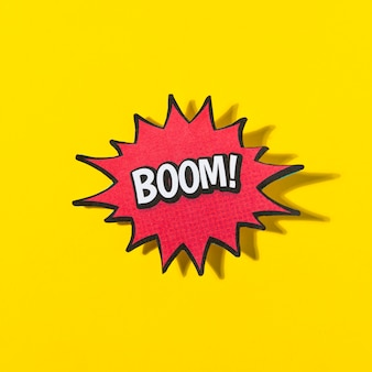 Palabra boom en burbuja de discurso cómico retro sobre fondo amarillo