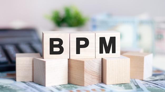 La palabra bpm en cubos de madera, billetes y calculadora en el fondo.