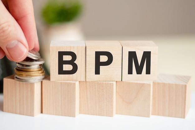 La palabra bpm escrita en cubos de madera. la mano de un hombre coloca las monedas en la superficie del cubo.