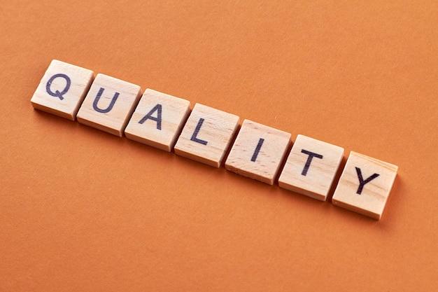 Palabra de calidad en bloques de madera. letras en cubos de madera aisladas sobre fondo naranja.