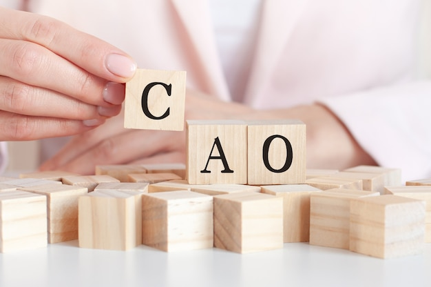La palabra cao en un juguete de madera bloquea con manos de mujer. cao abreviatura de director de contabilidad