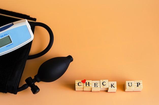 La palabra chesk up y un dispositivo para medir la presión sanguínea en naranja 2